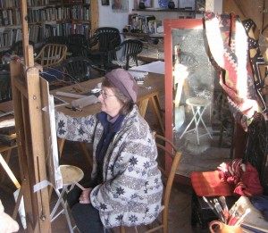 Anne at work with large vertical mirror behind and smaller to the right of her painting